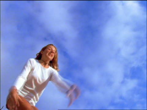 vídeos de stock e filmes b-roll de slow motion low angle girl jumping / blue sky in background - só uma menina adolescente