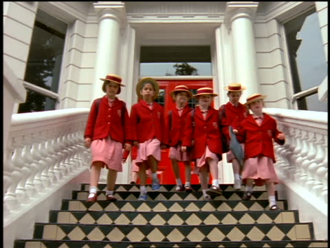slow motion low angle girls in red school uniforms walking down stairs of school towards camera / london - primary school child stock videos and b-roll footage