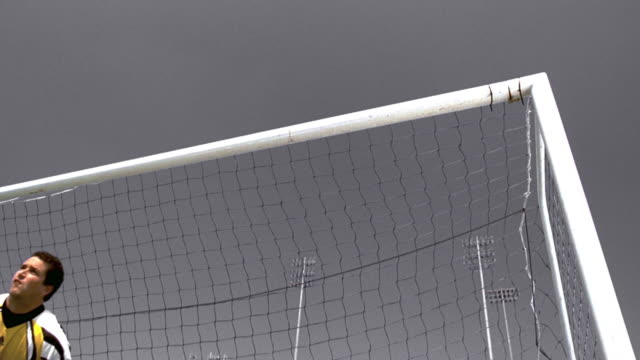 slow motion low angle ms goalie in yellow jersey jumping horizontally to block shot in soccer game - isolated colour stock videos & royalty-free footage
