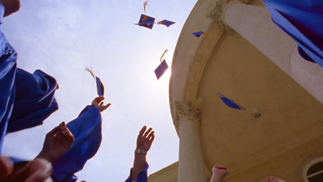 slow motion low angle graduates throwing caps in air + cheering / florida - latin american and hispanic stock videos & royalty-free footage