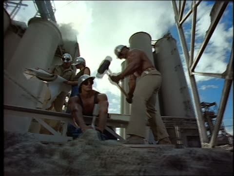 slow motion low angle PAN group of construction workers at industrial complex / one hammering