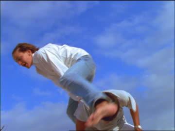 vídeos de stock, filmes e b-roll de slow motion low angle group of teens leapfrogging over man outdoors - jogo de carniça