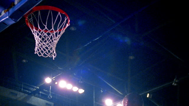 slow motion low angle heads + hands of two men's basketball teams looking up as ball goes in basket in arena
