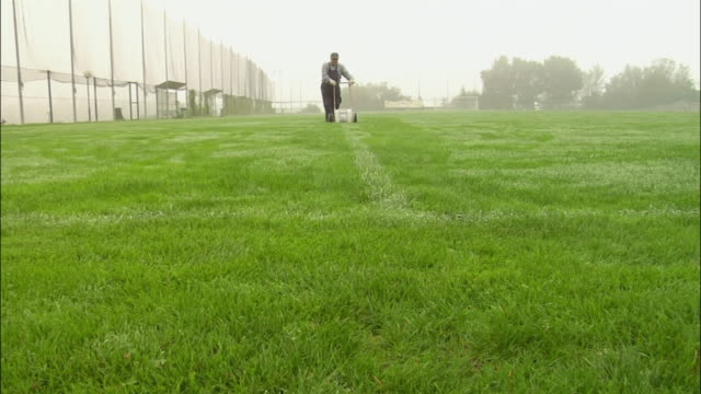 slow motion low angle long shot groundsman marking white lines on soccer field / two players jogging by and waving - pitch stock videos & royalty-free footage