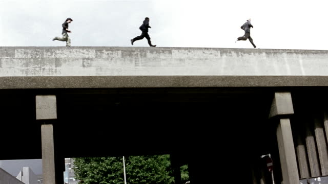 slow motion low angle long shot three freerunners running across bridge - 2004 stock videos & royalty-free footage