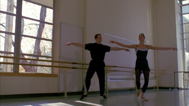 slow motion low angle male and female ballet dancers jumping by window - ballettstange stock-videos und b-roll-filmmaterial