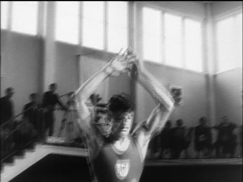 b/w 1960 slow motion low angle male gymnast bouncing on trampoline in championship / germany / newsreel - only mid adult men stock videos & royalty-free footage