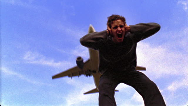 vídeos de stock, filmes e b-roll de slow motion low angle ms man bent over screaming + shaking head with hands over ears as airplane flies overhead - desconfortável