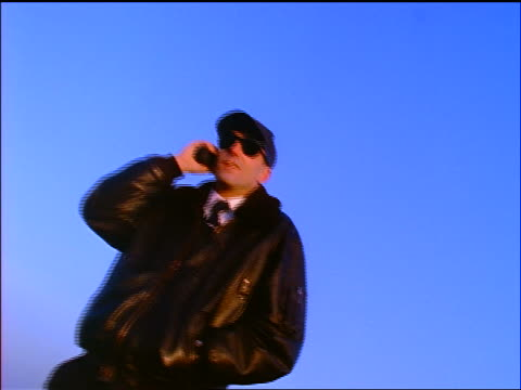 slow motion low angle man in black leather jacket with cellular phone walking past camera as airliner flies above - 1998 stock-videos und b-roll-filmmaterial