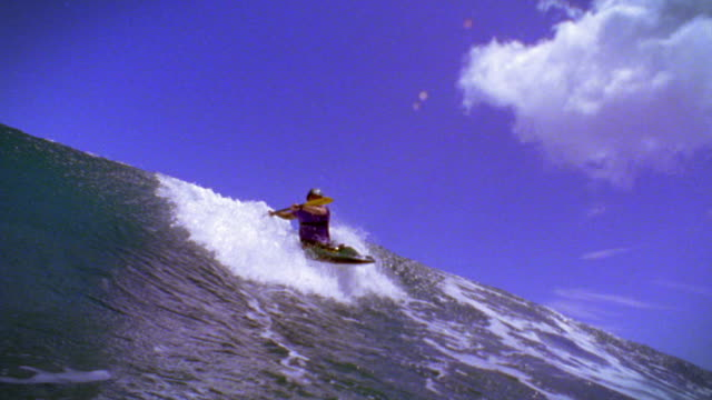 slow motion low angle PAN man in kayak in ocean riding huge wave / water washes over camera / Hawaii