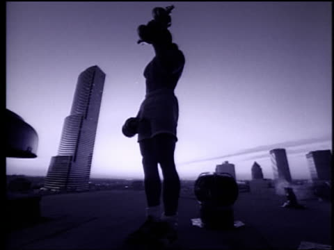 b/w slow motion low angle man lifting dumbbells on roof at sunset / centrust tower in background / miami - arm curl stock videos and b-roll footage