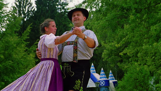 slow motion low angle man + woman in german costumes dancing on stage in park / bad kohlgrub, bavaria - traditional ceremony stock videos & royalty-free footage
