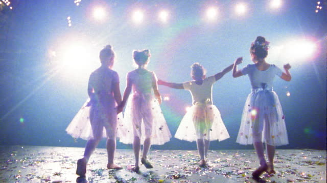 Slow motion low angle medium shot ballerinas holding hands and bowing w/confetti on floor / spinning w/hands above head