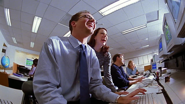 Slow motion low angle medium shot businessman and woman pointing to computer (off screen) / laughing / man talking on phone