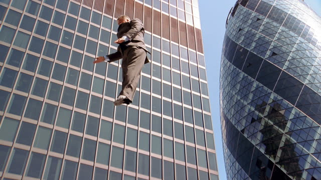 vidéos et rushes de slow motion low angle medium shot businessman bouncing in air against buildings in background / flipping in air - souplesse