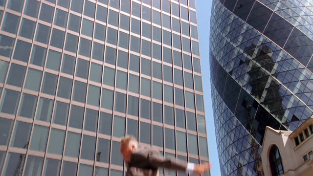 vidéos et rushes de slow motion low angle medium shot businessman bouncing in air against background / flipping in air - agilité entreprise