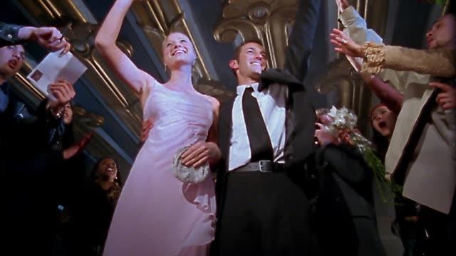Slow motion low angle medium shot famous couple waving / signing autographs
