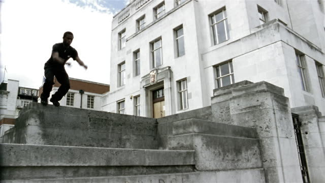 Slow motion low angle medium shot freerunner jumping off one ledge and landing on another / flipping off