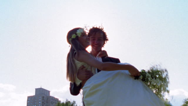 slow motion low angle medium shot groom carrying bride with bride throwing bouquet and sun flare / nyc - bride 個影片檔及 b 捲影像