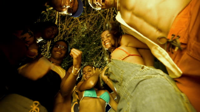 slow motion low angle medium shot group of young people dancing around cam outdoors at night - cleavage breasts stock videos and b-roll footage