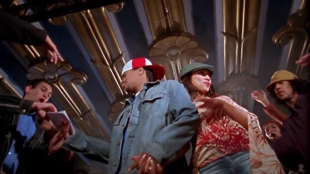 Slow motion low angle medium shot hip hop stars signing autographs / waving / shaking hands