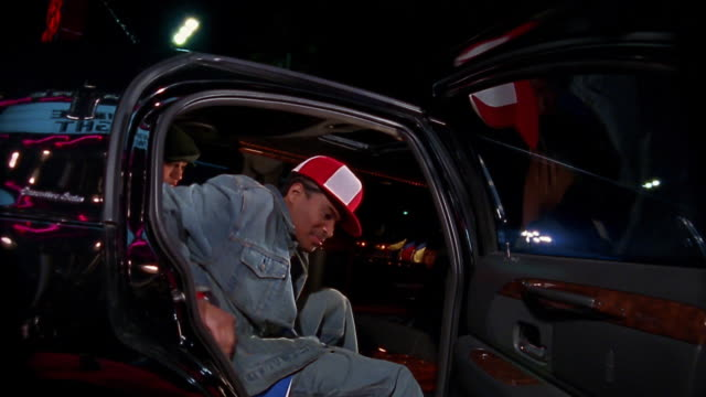 Slow motion low angle medium shot man opening limo door / hip hop couple getting out of limo