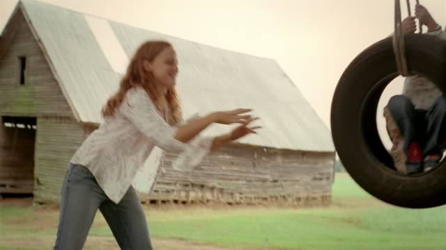 slow motion low angle medium shot pan girl pushing younger girl on tire swing near barn and old-fashioned gas pump - tyre swing stock videos & royalty-free footage