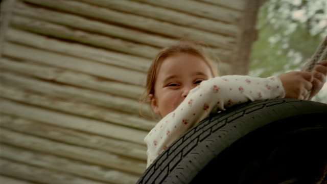 slow motion low angle medium shot pan girl pushing younger girl on tire swing near barn and old-fashioned gas pump - tire swing stock videos & royalty-free footage