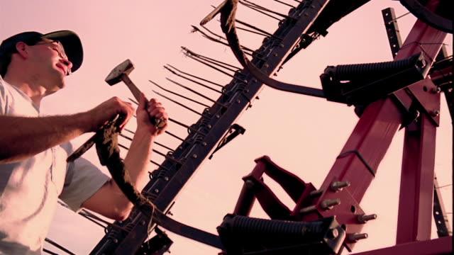 vídeos y material grabado en eventos de stock de slow motion low angle medium shot pan man hammering piece of farm machinery outdoors / clarksville, iowa - un solo hombre de mediana edad