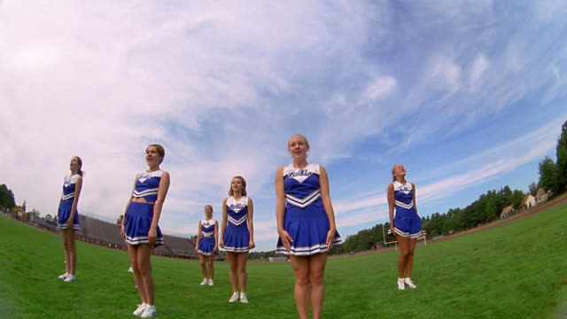 slow motion low angle medium shot pan teen female cheerleaders in uniform cheering, turning and raising arms on field - cheerleader stock videos and b-roll footage