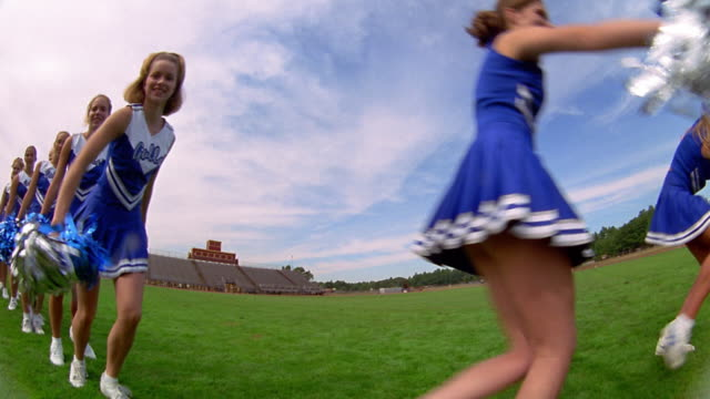 slow motion low angle medium shot teen female cheerleaders in uniforms shaking pom poms at camera on field - cheerleader stock videos & royalty-free footage