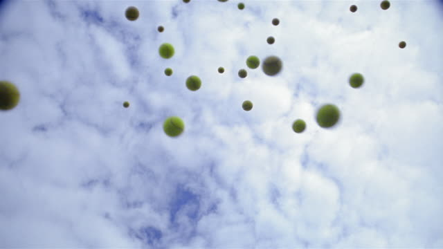vídeos de stock e filmes b-roll de slow motion low angle medium shot tennis balls flying in the air with cloudy sky in background - bola de ténis