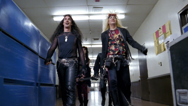 Slow motion low angle medium shot tracking shot glam band walking in hallway backstage / close up of boots