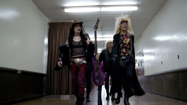 slow motion low angle medium shot tracking shot glam band walking in hallway backstage / raising their instruments - klassischer rock and roll stock-videos und b-roll-filmmaterial