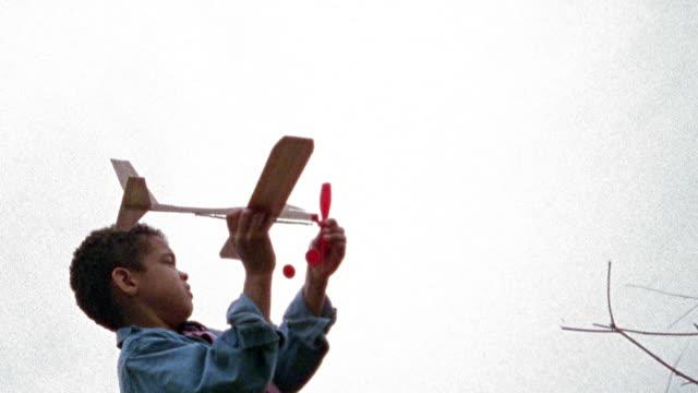 slow motion low angle medium shot young black boy throwing toy airplane in rain / missouri - model aeroplane stock videos & royalty-free footage