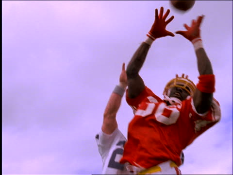 slow motion low angle of 2 football players jumping to catch ball - american football ball stock videos & royalty-free footage