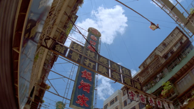 slow motion low angle of airliner flying over buildings and signs / hong kong - cinematografi bildbanksvideor och videomaterial från bakom kulisserna