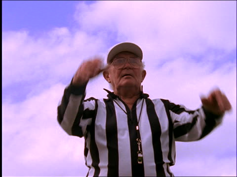 "slow motion low angle of football referee signaling ""holding"""