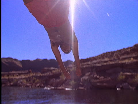 slow motion low angle of man diving over camera into lake - cinematography stock videos & royalty-free footage