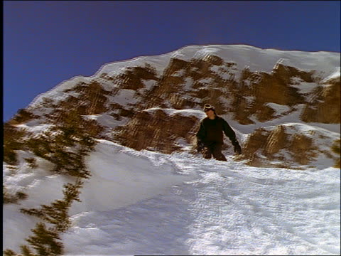 slow motion low angle of man on snowboard jumping off cliff