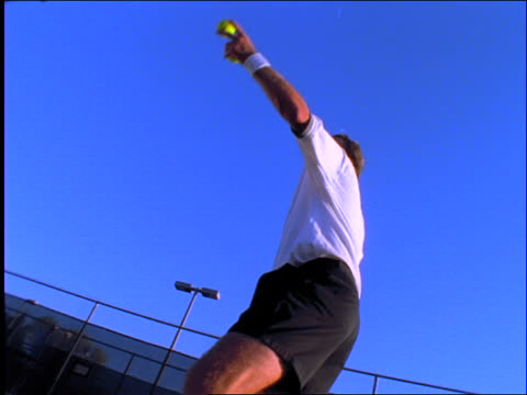 slow motion low angle of man serving tennis ball in match