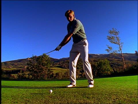vídeos de stock, filmes e b-roll de slow motion low angle of man teeing off on golf course - camisa pólo