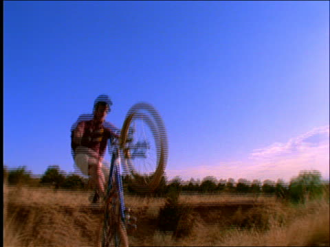 slow motion low angle of mountain biker jumping over camera - anno 1997 video stock e b–roll