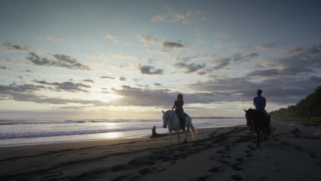 Slow motion low angle panning shot of couple riding horseback on beach / Esterillos, Puntarenas, Costa Rica