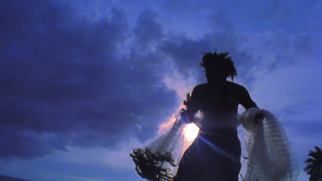 blue slow motion low angle profile silhouette of man throwing net into ocean / hawaii - fisherman stock videos and b-roll footage