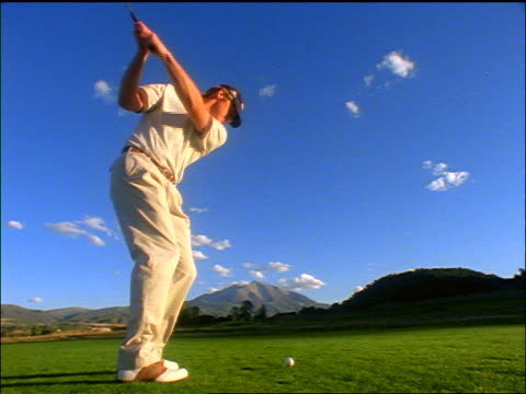 slow motion low angle rear view man hitting golf ball on fairway / mountains in background / colorado - golf swing stock videos & royalty-free footage