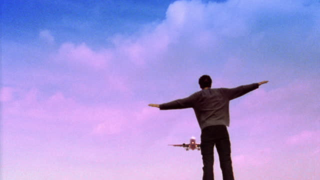 slow motion low angle rear view man spreading arms with airplane flying overhead / belgium - onirico video stock e b–roll