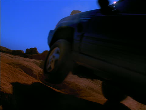 slow motion low angle rear view off-road vehicle driving up bumpy hill in desert - bumpy stock videos & royalty-free footage