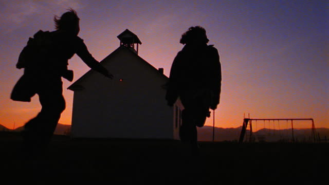 slow motion low angle REAR VIEW silhouetted 3 children running toward swings by schoolhouse at twilight/ Montana