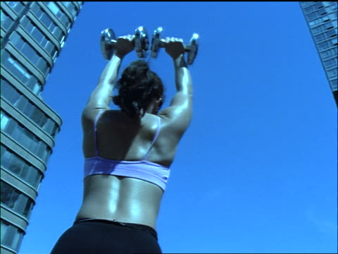 blue slow motion low angle rear view tilt up tilt down woman lifting dumbbells above head on roof of building / nyc - hand weight stock videos & royalty-free footage